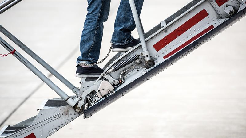 cropped image of shackled feet walking up the stairs to a plane