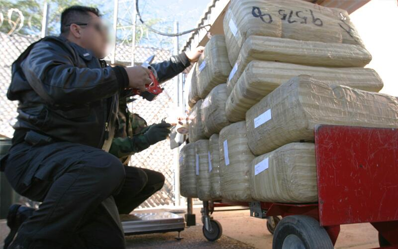 ICE special agents inspect a seized drug shipment during Operation Shadow Wolves.