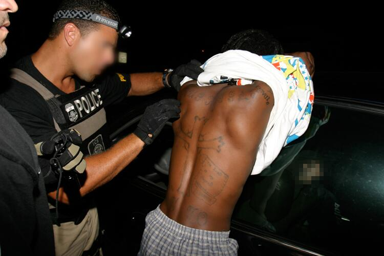 ICE officers check a suspect's tattoos for gang references.