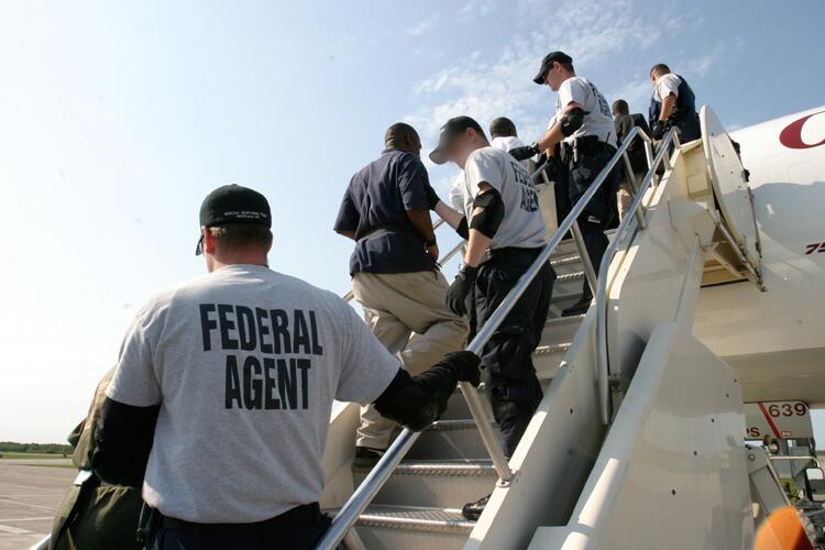 ICE agents escort illegal aliens as they board a plane.