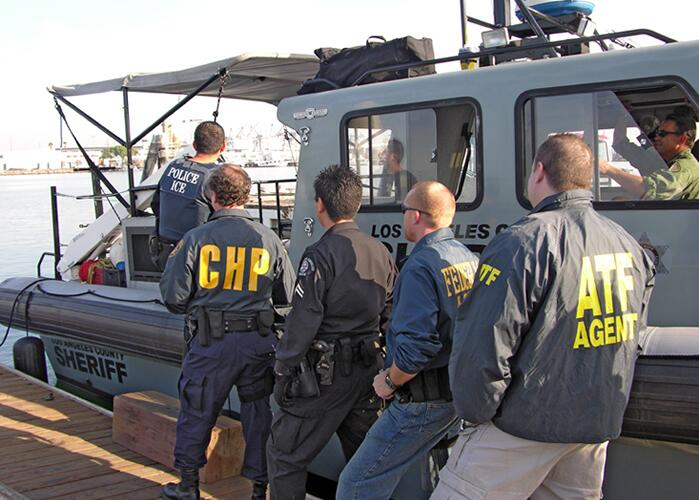 An ICE officer boards a vessel with federal partner agencies.