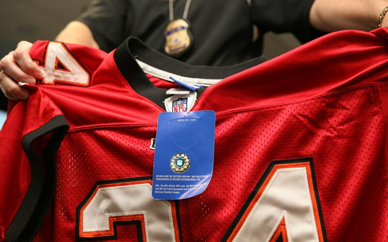 An ICE special agent displays a counterfeit professional football team jersey.