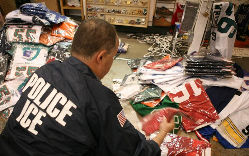 An ICE special agent lays out confiscated counterfeit merchandise.