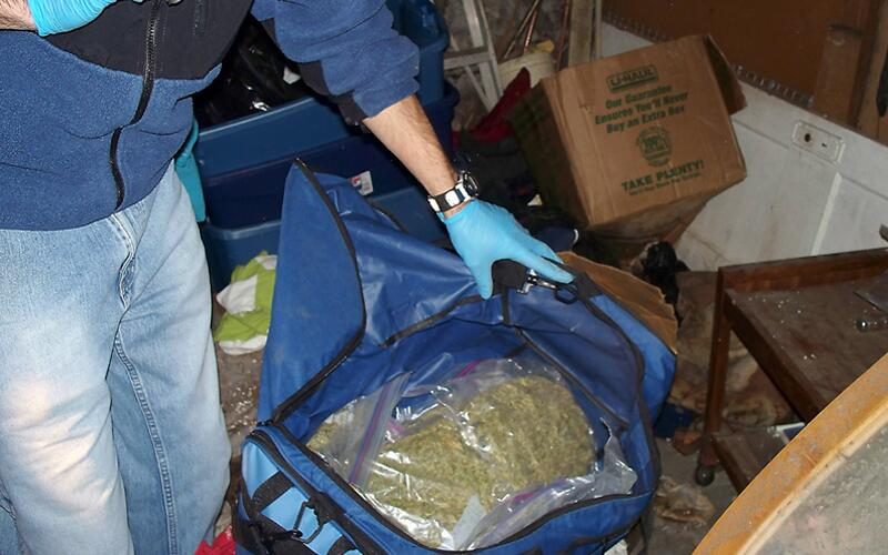 An ICE official inspects confiscated narcotics.