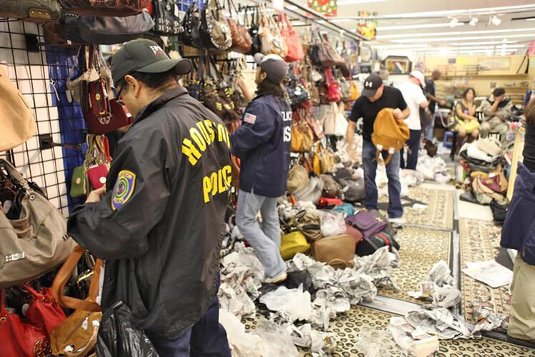 HSI special agents survey counterfeit designer apparel.