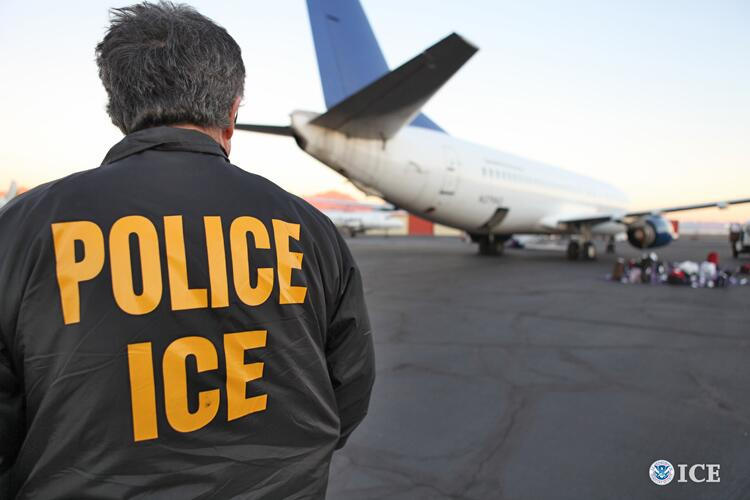 An ICE ERO officer stands on an airport tarmac during an enforcement operation.
