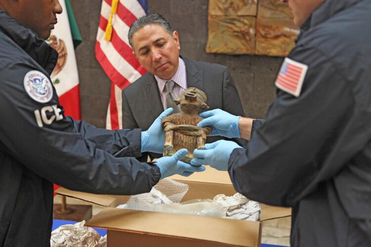 HSI special agents display an artifact at a Mexican repatriation ceremony.