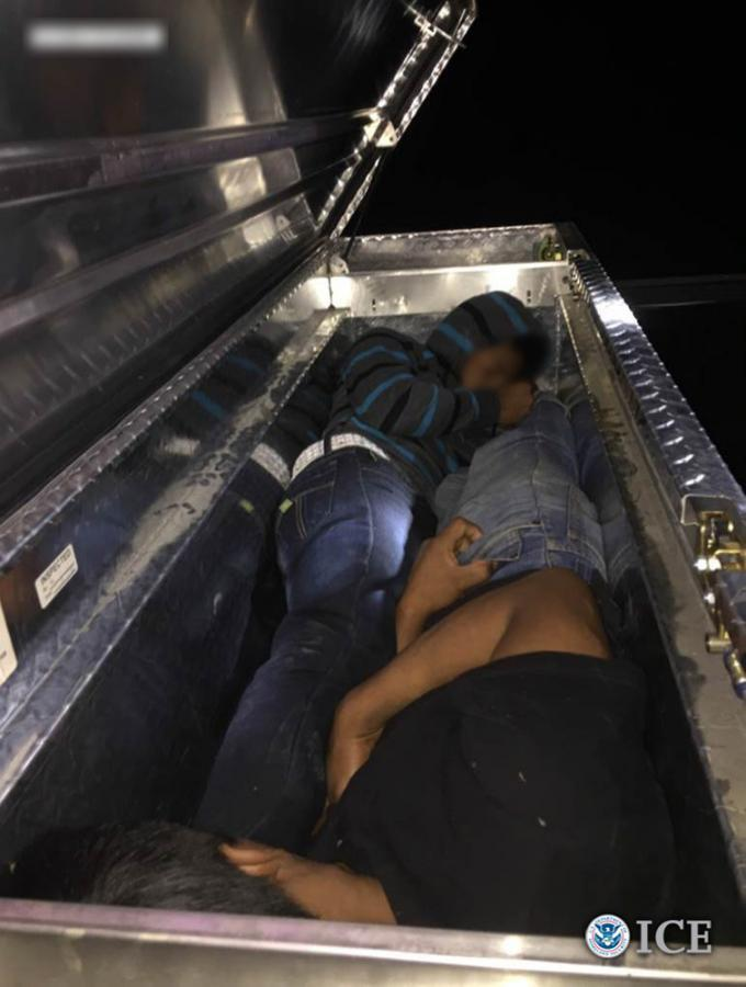 Two illegal aliens hiding in the tool box of a pick-up truck while being transported by smugglers after crossing the border.