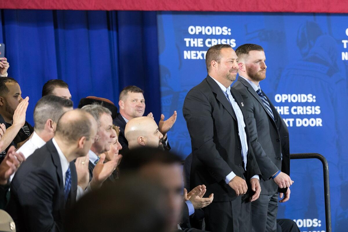 President Donald J. Trump recognizes law enforcement officers, HSI-Boston Special Agent Ronald Morin (left) and Manchester, NH, police detective Patrick Maguire, as he deliver remarks on combating the opioid crisis at Manchester Community College, Monday, March 19, 2018, Manchester, NH.