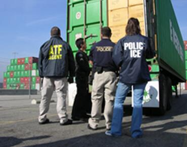 ICE and ATF officials standing in front of a shipping container