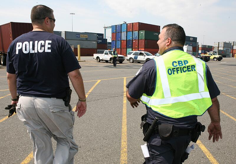 BEST: Police and CBP Officer walking toward shipping containers
