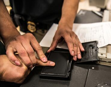 ICE Officer taking fingerprints