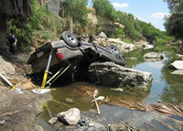 An example of the mayhem of human smuggling; this truck overturned when smugglers jumped out and left their human cargo to crash into the river.