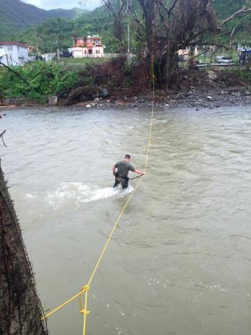 A special agent with HSI New York's Special Response Team wades through a river to reach Juana Dias, PR. Even with the bridge out, the team crossed to meet the helicopter that was landing with food and water on the other side.