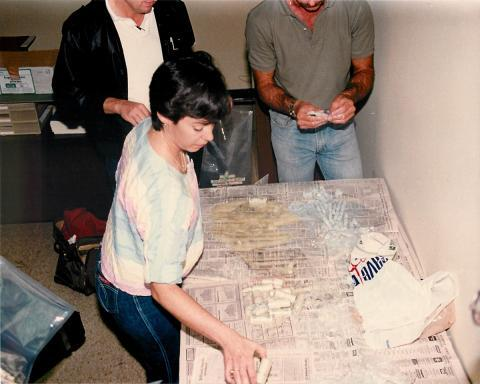 "Agent Cannon and others unpack tightly wrapped rolls of money hidden, then taken out of shampoo, conditioner and body wash bottles in the U.S. Customs Miami, Outbound Currency ""Buckstop"" Group Office, 1985. The items were seized from outbound luggage to Colombia."