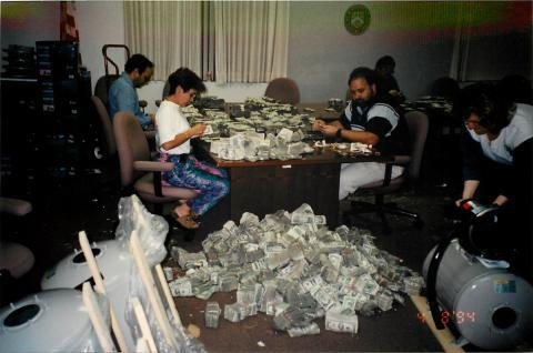 U.S. Customs Service agents at the federal complex in Doral, Florida, on a Friday night in April 1994, counting and bundling money. It took all night to process the $10 million seized in outbound airport cargo of water pumps and outdoor speakers.