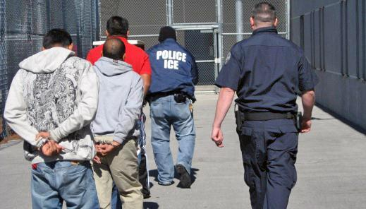 ICE agents escort three of the 95 arrested individuals towards incarceration