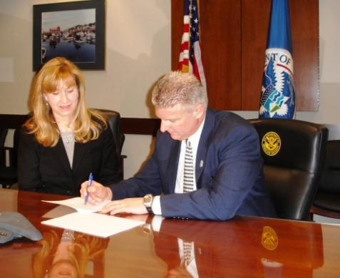 Kathleen Guinee, owner of Aetna Fire Alarm Service Company, Inc., signs an IMAGE agreement.