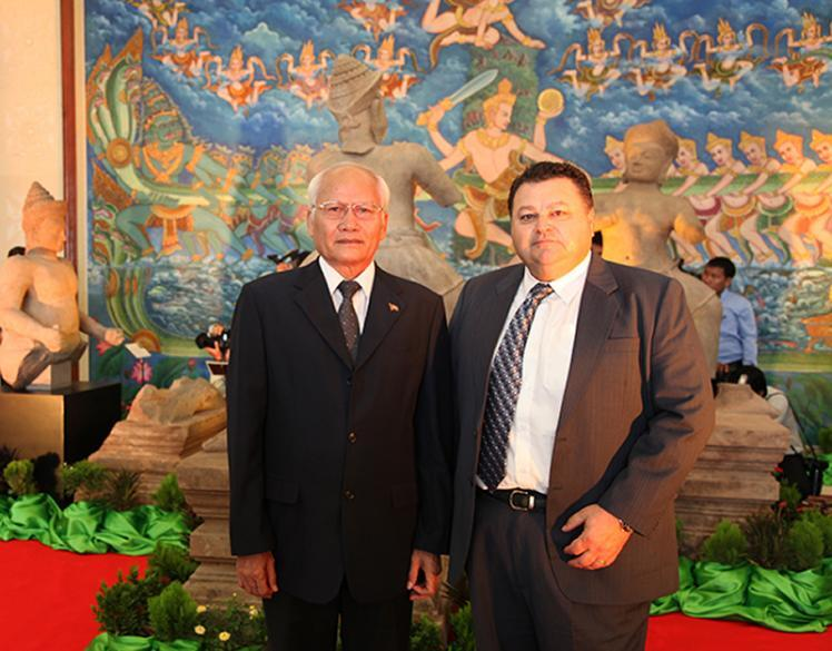 photo of HSI Phnom Penh Attaché JP Galoski with His Excellency, Chuch Phoeun, Secretary of State for the Ministry of Culture posing in front of the statues prior to commencement of the ceremony