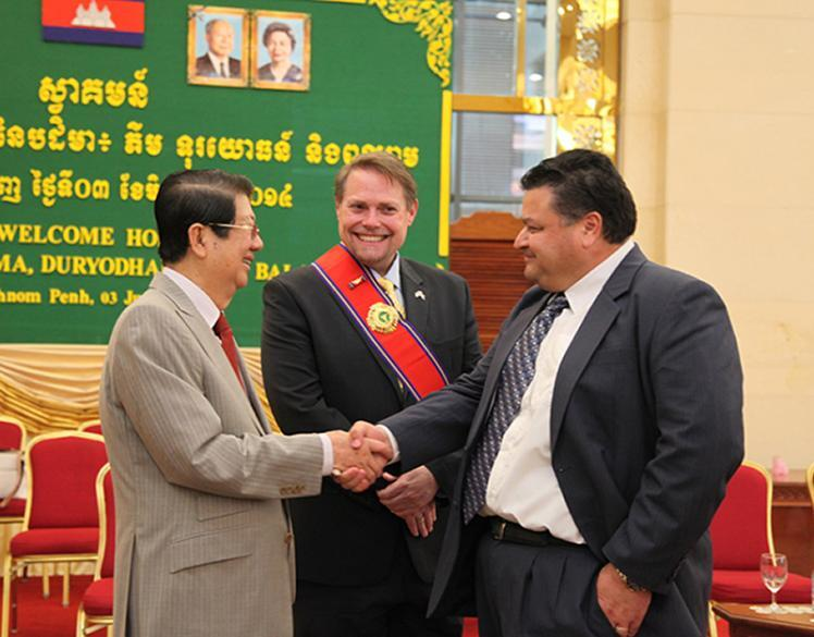 photo of HSI Phnom Penh Attaché JP Galoski shaking the hand of Deputy PM Sok An with DCM Jeff Daigle looking on at the conclusion of the ceremony