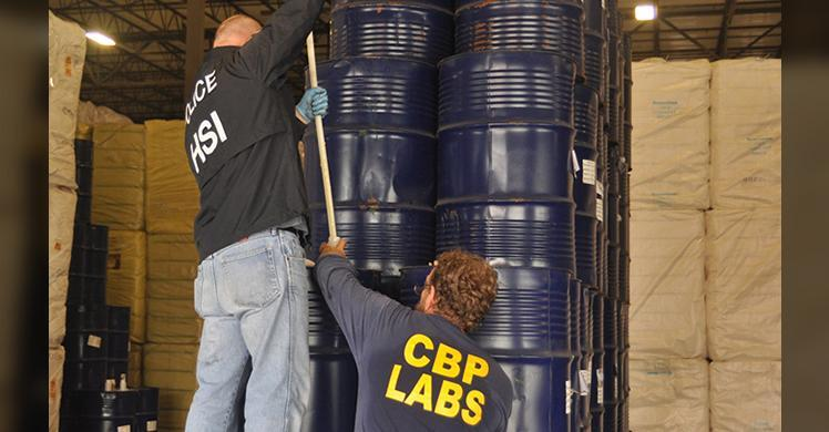 HSI special agent and CBP officer inspecting seized honey.
