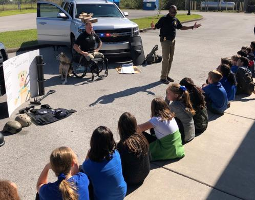 HSI Tampa Special Agent Alvis Lockhart and Computer Forensic Analyst Justin Gaertner and his service dog Gunner presented to Tampa Bay area children during the Great AmericanTeach-In