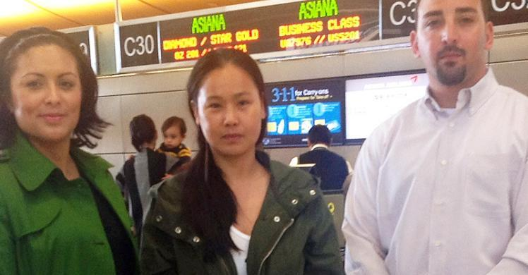 Flanked by ERO escorts, South Korean woman wanted in her native country on prostitution charges prepares to depart LAX.