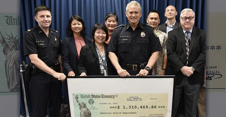 Hawaii U.S. Attorney Florence T. Nakakuni (front left) delivers check to Honolulu Police Chief Louis Kealoha joined by Honolulu SAC Joanna Ip (back row, second from left) and other federal agency representatives.