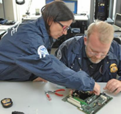 HSI special agents gather data off a computer at the new forensic lab in Boston
