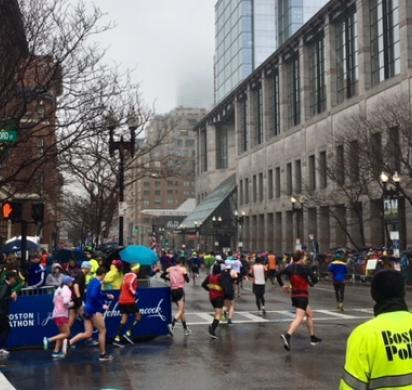 Runners in the 2018 Boston Marathon make their way on to Boylston Street, site of the 2013 bombing, as Boston Police look on.