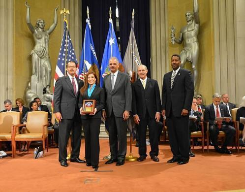 Special Agent Liza Lugo, HSI Tucson, receives an award from U.S. Attorney General Eric Holder with HSI Executive Associate Director Peter Edge (right).