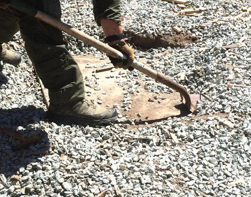 Agent clears rocks away from a wood plank covering the tunnel opening