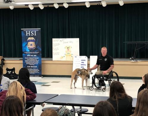 HSI Tampa Computer Forensic Analyst Justin Gaertner and his service dog Gunner presented to Tampa Bay area children during the Great American Teach-In