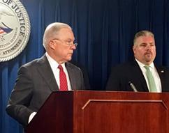 U.S. Attorney General Jeff Sessions applauds the work of HSI Boston's Document and Benefit Fraud Task Force while Peter Fitzhugh, Special Agent In Charge, HSI Boston looks on; U.S. Attorney's Office, Boston, July 26