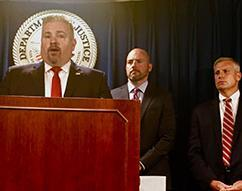 Peter Fitzhugh, HSI Boston special agent in charge (left) listens as U.S. Attorney for Massachusetts Andrew E. Lelling (center) announces indictment and arrest;    Harold H. Shaw, special agent in charge, FBI Boston Field Division is at right)